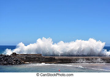 crashing wave on seawall - A big wave crashing on a seawall