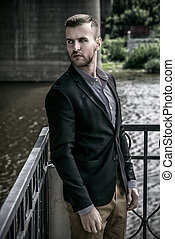 by the river - Elegant well-dressed man standing on the...