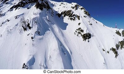 Quadrocopter shoot snowboarder freestyle from peak of snowy...