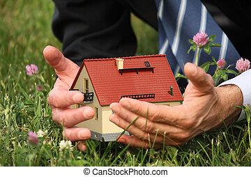 Mans hands holding house miniature, grass, clover flowers...