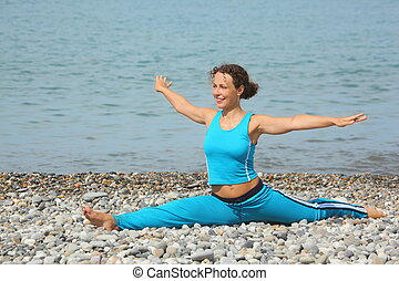 joyful woman wearing sporty clothers is smiling and stretching on sea coast.