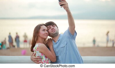 Beautiful couple taking selfie giving kiss on the beach on summer