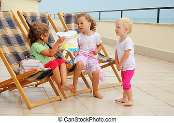 Three little girls in lounge on veranda, considering drawing
