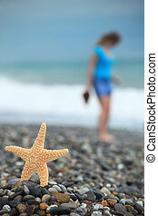 Starfish and young girl on stone seacoast