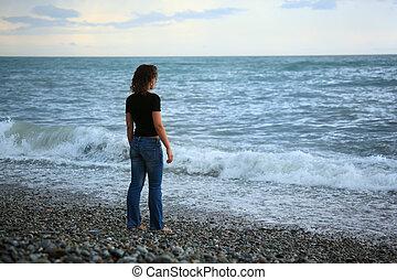 beautiful woman on stone stone seacoast, Standing back