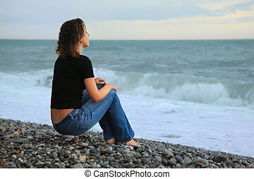 beautiful woman on stone stone seacoast, sitting by back