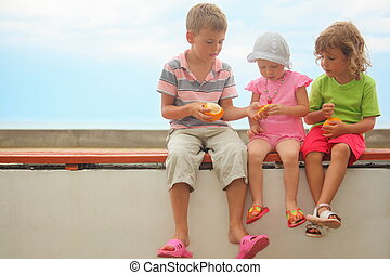 children: boy and two girls sitting on a brach. skin of...