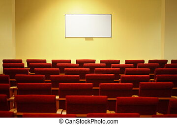 empty conference hall with screen. rows of a chairs. focus on a screen.