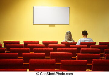 empty conference hall. rows of a chairs. focus on a third row. man and woman sitting in chairs
