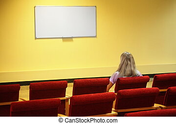 woman sitting in a chair in a first row of empty presentation hall. screen in out of focus. focus on a woman.