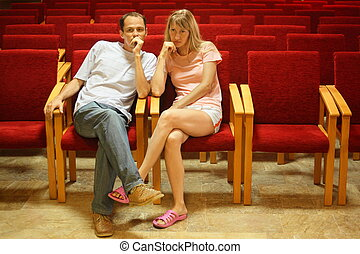 man and woman sitting on a chairs in empty presentation...