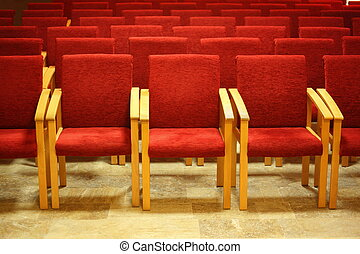 rows of a chairs in empty presentation hall. focus on a chairs in first row.