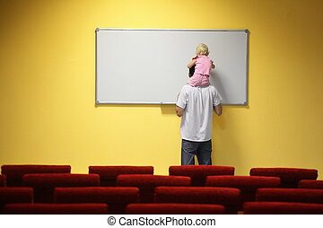 little girl is sitting on father\'s neck and drawing on a board. chair in out of focus.