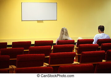 family in empty presentation hall is waiting start of showtime. screen in out of focus. focus on a woman.