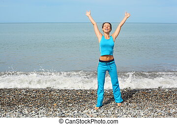 joyful woman wearing sporty clothers with raised hands on...