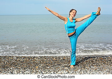 joyful woman wearing sporty clothers stretching on sea coast