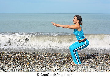 joyful woman wearing sporty clothers is making exercise on sea coast. she is squating.