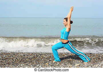 woman wearing sporty clothers is making exercise on sea coast and looking away