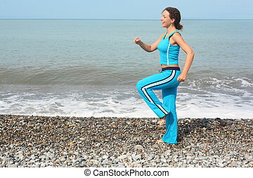 smiling woman wearing sporty clothers is making exercise on sea coast