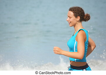 joyful woman wearing sporty clothers is running. sea in out of focus.