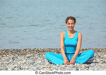 smiling woman is stretching on a coast of sea. she is wearing sporty clothers.