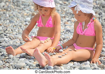 two little girls is playing with pebble stones. focus on...