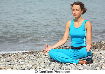 joyful woman wearing sporty clothers is meditate on a sea...