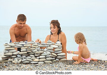 father, mother and little girl near construction of pebbles...