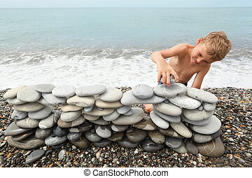 little boy is building construction of many pebbles on a sea...