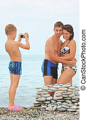 family on sea coast little boy with photocamera is making...