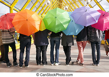 seven teens with opened umbrellas in pedestrian overpass...