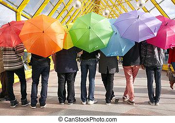 seven teens with opened umbrellas in pedestrian overpass....