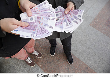 two teens staying with funs of euro in their hands