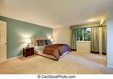Mint and brown bedroom with beige carpet floor.
