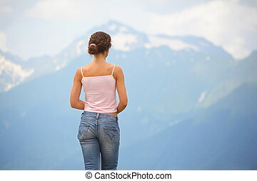 beautiful woman wearing t-shirt and jeans looking at mountains