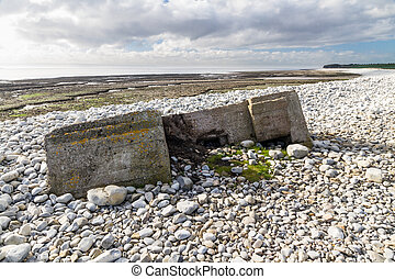 World War Two Pillbox sinking into pebbled beach, Aberthaw -...