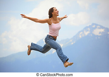 woman is jumping with her hands wide apart. mountains behind...