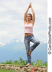 beautiful woman practise yoga. mountains in background.