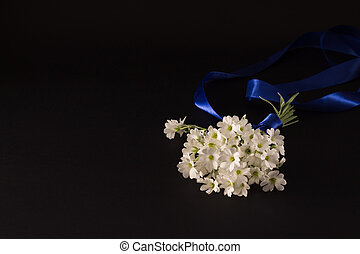 bouquet of small white flowers with a blue ribbon on a black background