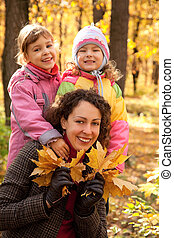 Woman with two small girls and maple leaves in autumnal park