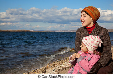 Mother and daughter sit near the lake and look at water