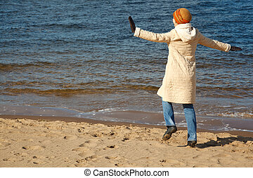 Cheerful girl walks on beach in solar autumn day. In coat, cap and jeans.