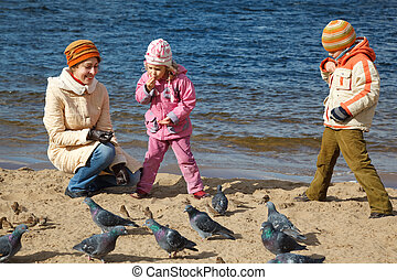 Boy and girl together with mum feed birds on autumn beach. Productive leisure in open air.