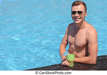 Joyful guy relaxing with drink in water - Cheerful young man...
