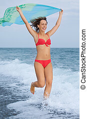 beautiful young woman with fabric running on stony beach