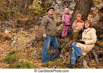 Mother, daughter, son and grandfather in autumnal forest near the tree