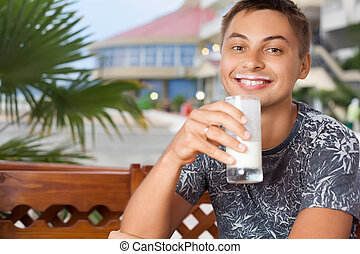 young smiling man sitting in an arbour on resort, drinking...