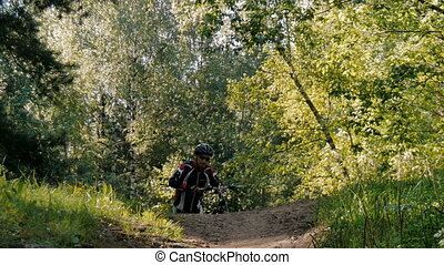 Cyclist rides through the forest, overcoming obstacles....