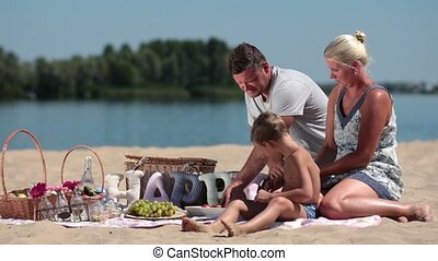 Family with child enjoying picnic on river bank during...