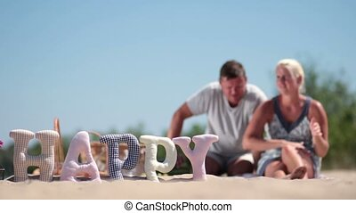 Blurred background of family having rest on beach -...